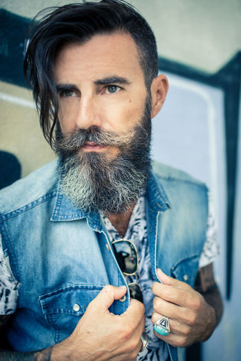 Close-Up Of Hipster Wearing Denim Jacket Against Wall