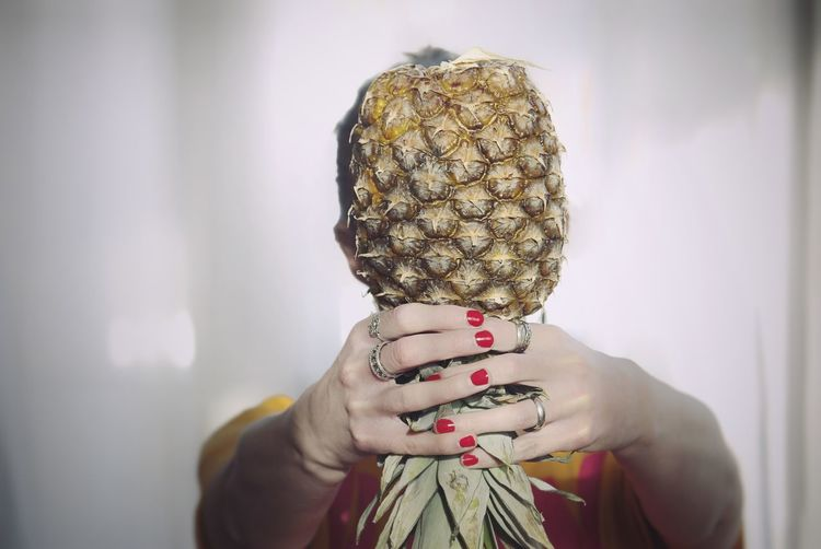 Woman holding pineapple in front of face