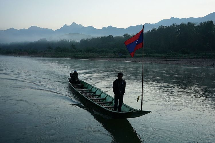 Man standing by flag in boat on lake against mountains
