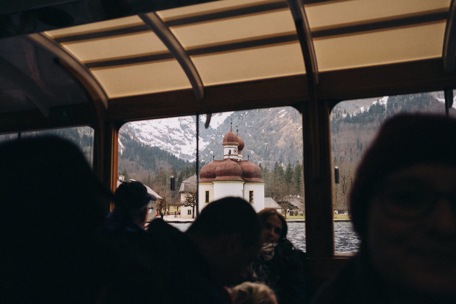 Chapel St. Barthomä viewed from a sightseeing boat on lake Königssee, Bavaria, Germany. Bavaria Church Königssee Schönau Am Königsee Silhouette Bavarian Alps Day Europe Friendship Germany Indoors  Journey Lifestyles Looking Through Window Men Mobile Photography Mountain Nature People Real People Sky Travel Destinations Vacations Window Women