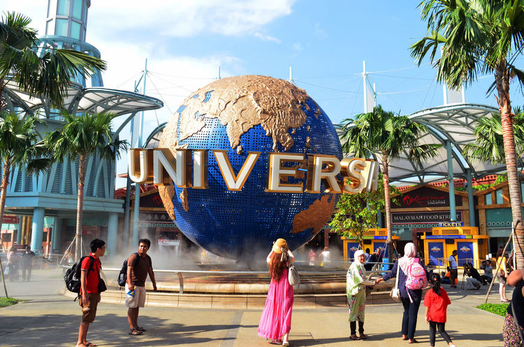 "the ""Universe"" with big world design found in Pulau Sentosa, Singapore. Adult Amusement Park Day Leisure Activity Men Outdoors Palm Tree People People Watching Plant Real People School Holidays Single Flower Sky Tourism Tree Wording"