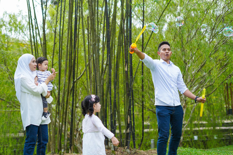 Playful family spending time together at park. Group Of People Men Standing Togetherness Plant Three Quarter Length Offspring Males  Women Tree Childhood Adult Emotion Child Casual Clothing Boys Nature Happiness Day Smiling Son Daughter