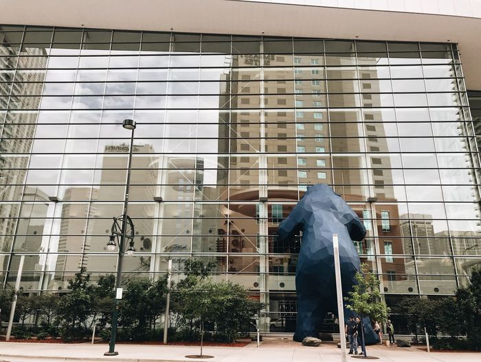 Low angle view of statue against modern building in city