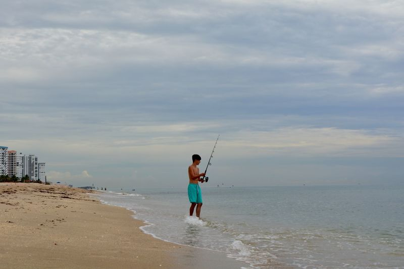 Man fishing while standing on shore at beach against sky