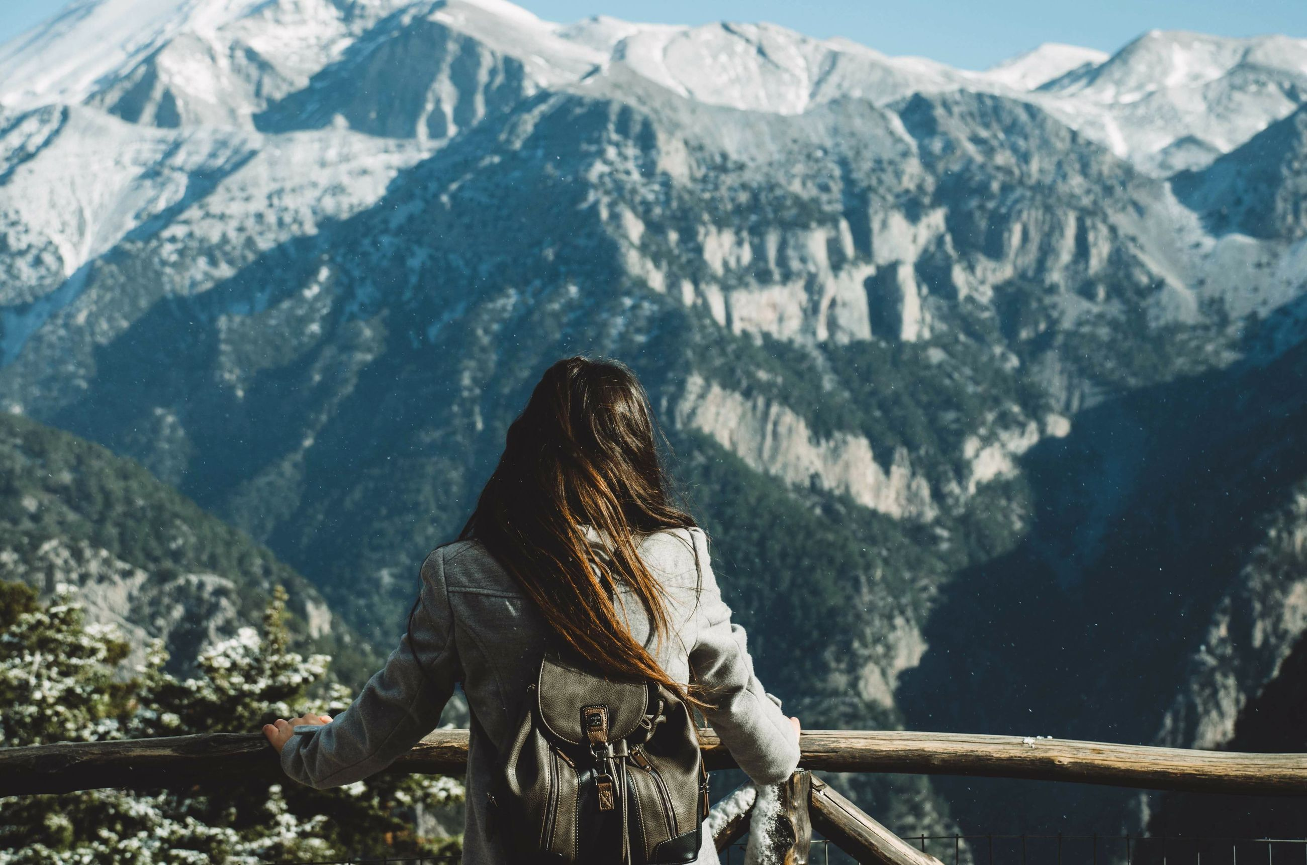 one person, mountain, mountain range, scenics - nature, leisure activity, real people, beauty in nature, lifestyles, sitting, nature, adult, rear view, women, day, environment, railing, adventure, three quarter length, tranquil scene, looking at view, outdoors, hairstyle