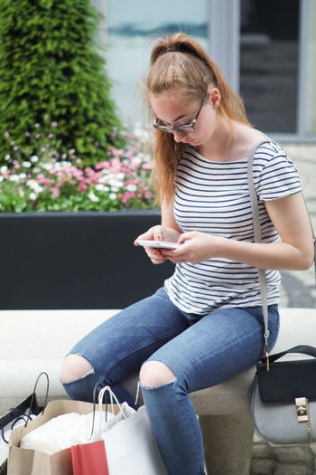 Casual Clothing Communication Front View Glasses Hairstyle Holding Leisure Activity Lifestyles Mobile Phone Outdoors Schoping Shopping Bags Shopping Break Sitting Smart Phone Technology Teenager Texting Using Mobile Phone Using Phone Wireless Technology