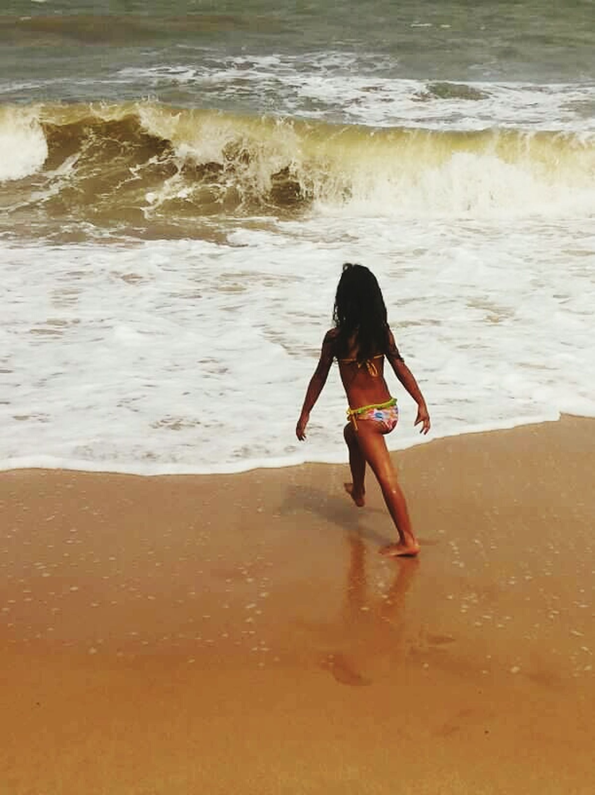 beach, sand, shore, wave, surf, sea, water, vacations, tourism, tide, one person, coastline, tourist, summer, carefree, travel destinations, weekend activities, one girl only, beach holiday, tranquility, enjoyment, getting away from it all, beauty in nature, nature, reaching, person