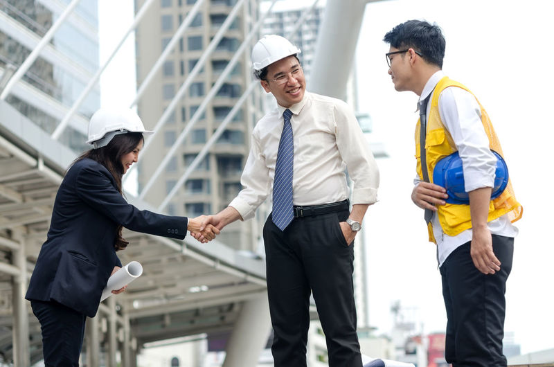 Engineers Shaking Hands With Man In City