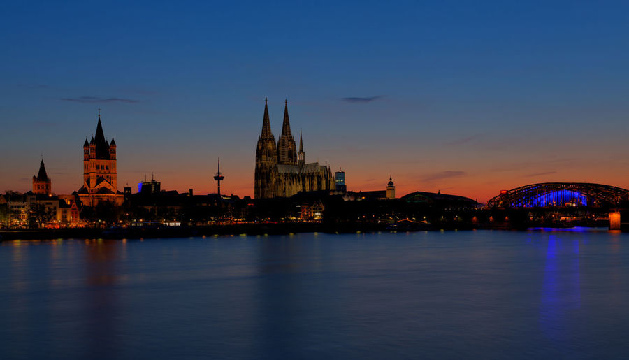 Buildings and cologne cathedral by rhine river in city at night