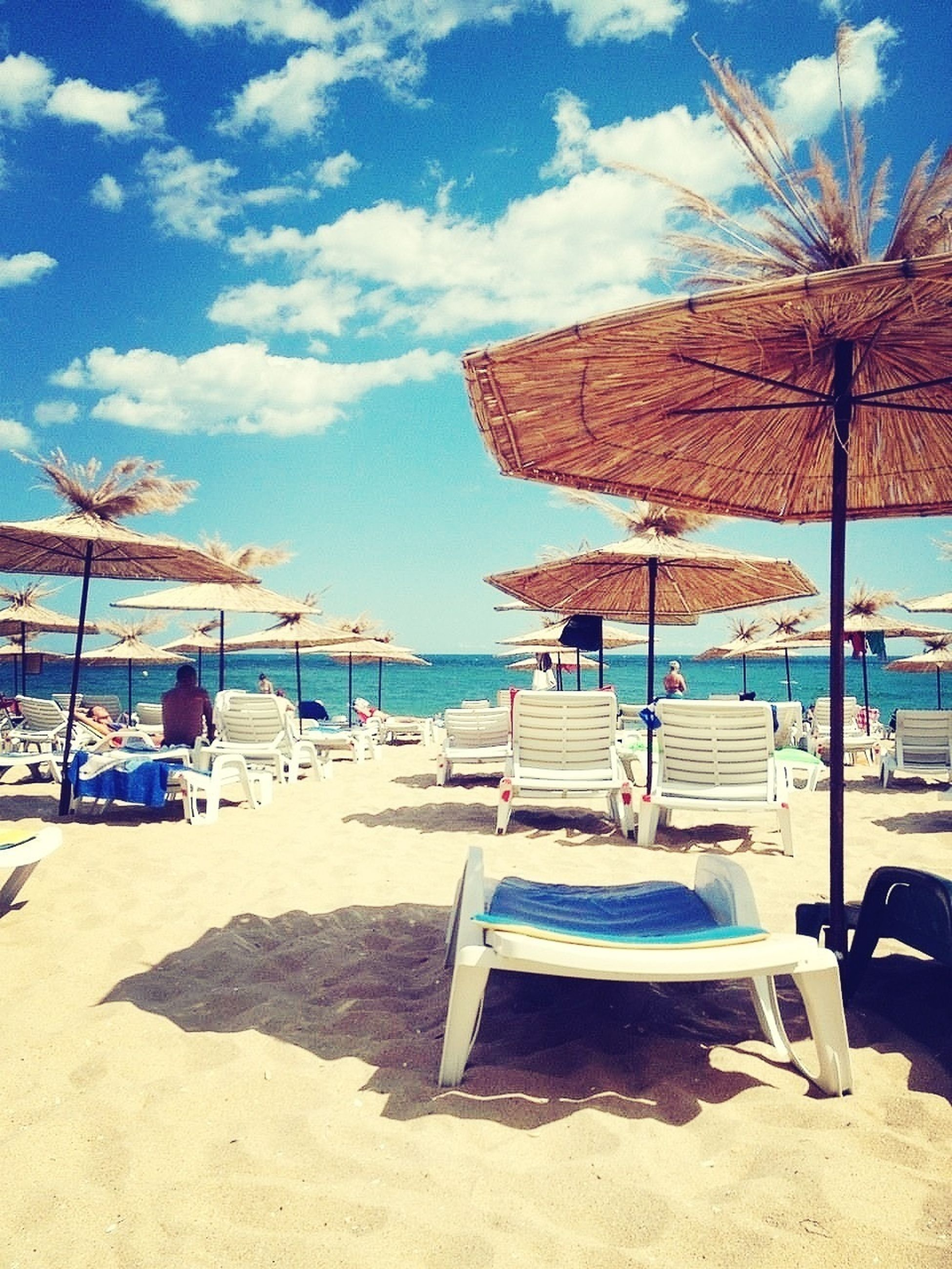 beach, sand, sea, shore, sky, beach umbrella, water, horizon over water, parasol, lounge chair, summer, sunshade, thatched roof, vacations, sunlight, blue, deck chair, relaxation, incidental people, absence