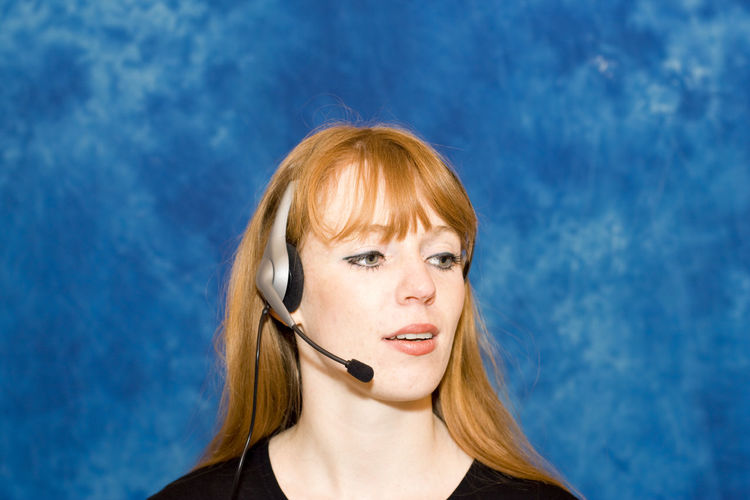 Businesswoman wearing headset in office against blue wall