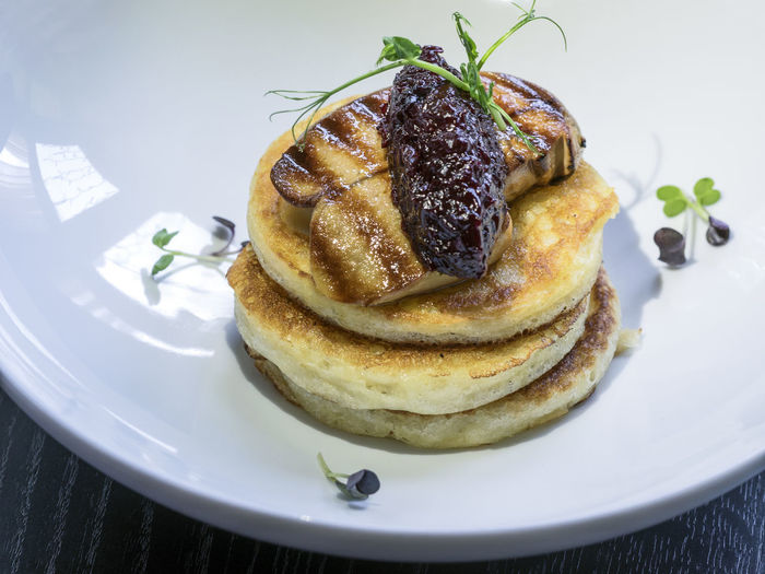 High Angle View Of Pancakes With Fried Foie Gras And Onion Marmalade On Table