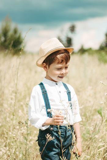Little farmer on a summer field, cute little boy in a straw hat. boy with a flower