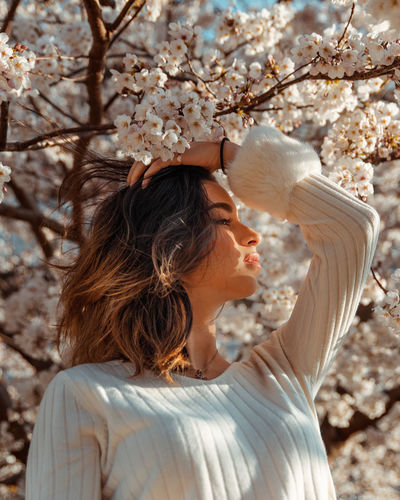 Side view of young woman looking away by flowers on tree