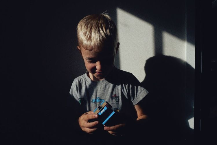 Close-up of boy playing with toy car