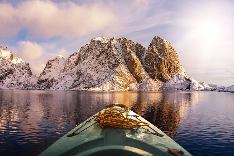 Scenic view of boat in lake against snowcapped mountains and sky