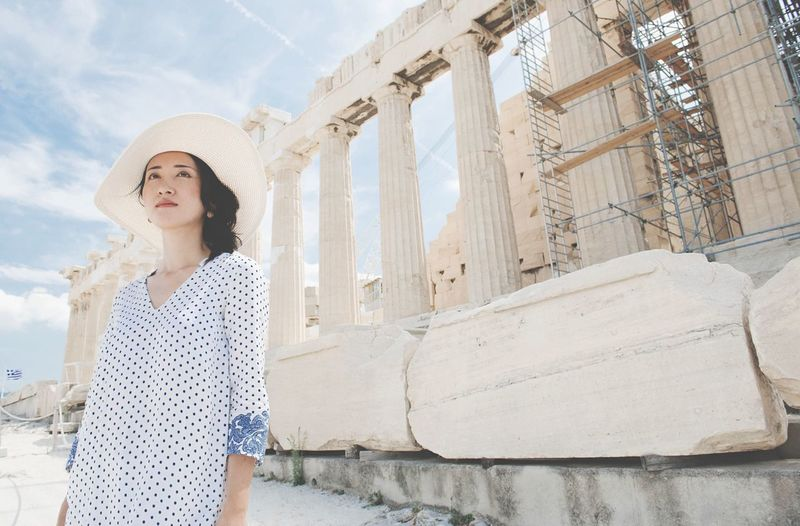 Low angle view of thoughtful young woman standing at acropolis