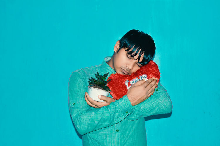 Black Hair Blue Blue Background Casual Clothing Colored Background Emotion Front View Hairstyle Holding Indoors  Looking One Person Positive Emotion Red Standing Studio Shot Turquoise Colored Waist Up Young Adult The Portraitist - 2018 EyeEm Awards The Still Life Photographer - 2018 EyeEm Awards The Creative - 2018 EyeEm Awards Capture Tomorrow