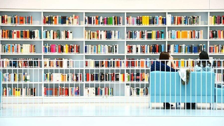 Rear view of people sitting on sofa in front of book selves at library