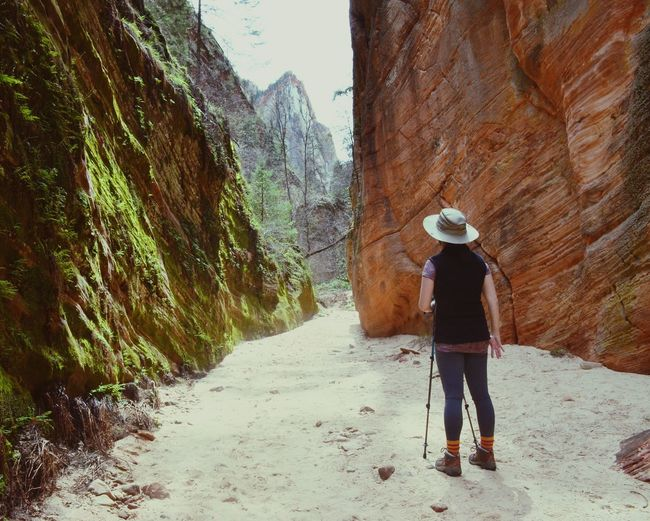 Rear View Of Woman Standing Amidst Rock Formation At Zion National Park