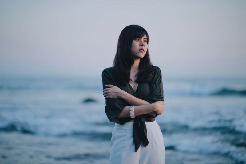 Thoughtful young woman hugging self while looking away at beach against sky