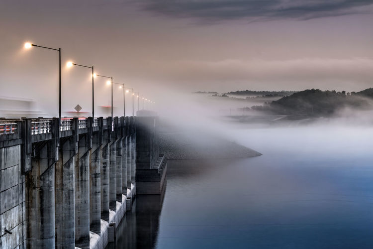Illuminated pier over lake against sky