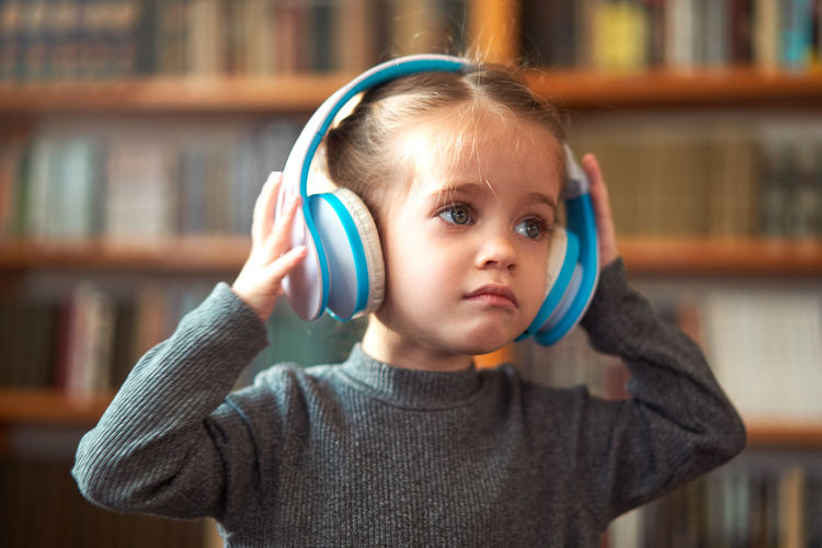 Close-up of girl wearing headphones at home