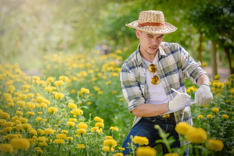 Young man with clipboard standing by yellow flowering plants