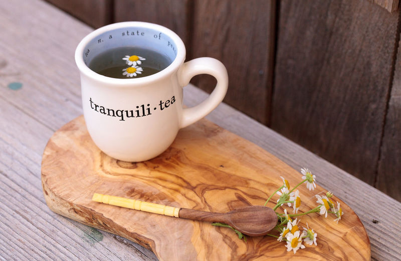 High angle view of chamomile tea with daisy flowers on cutting board