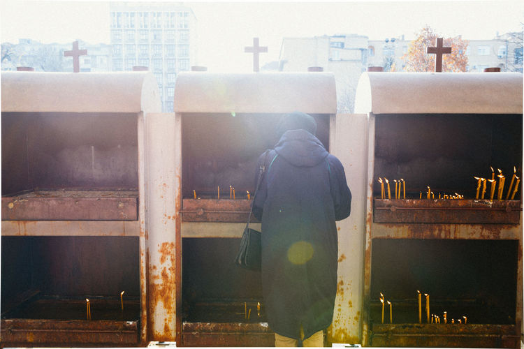 Rear view of woman with prayer candles
