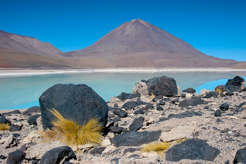 Black lava stones on the shore of Laguna Verde, Bolivia Beauty In Nature Blue Clear Sky Day Idyllic Laguna Verde Lake Mountain Mountain Peak Mountain Range Nature No People Non-urban Scene Outdoors Rock Rock - Object Salt Flat Scenics - Nature Sky Solid Tranquil Scene Tranquility Volcanic Crater Water