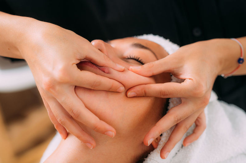 Woman enjoying a professional ayurvedic facial massage with therapeutic essential oils
