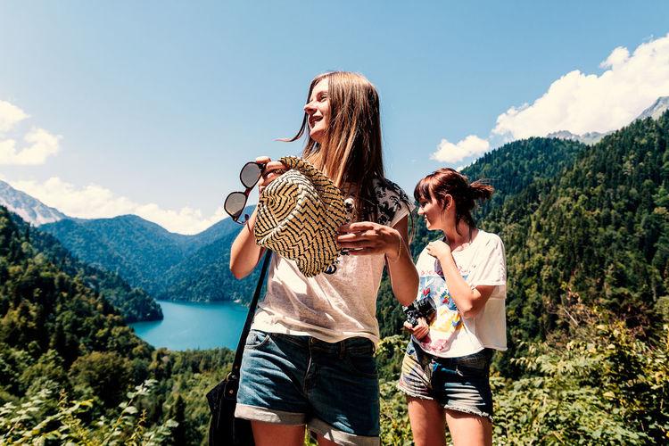 Girls Standing On Mountain Against Sky