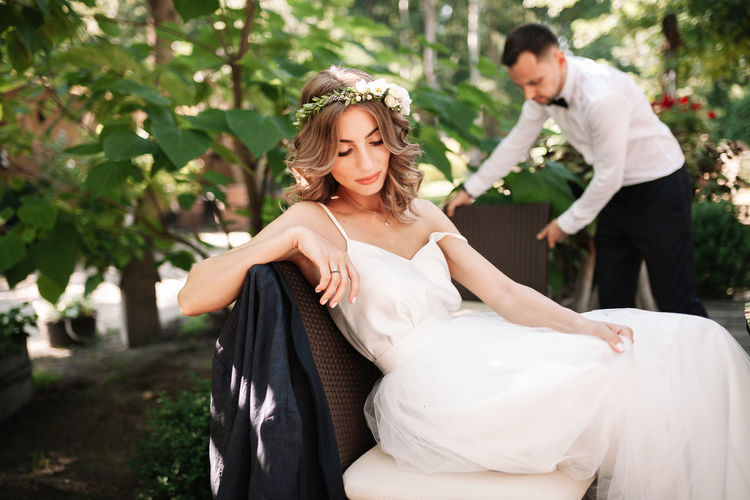 Beautiful bride sitting on chair with groom in background outdoors