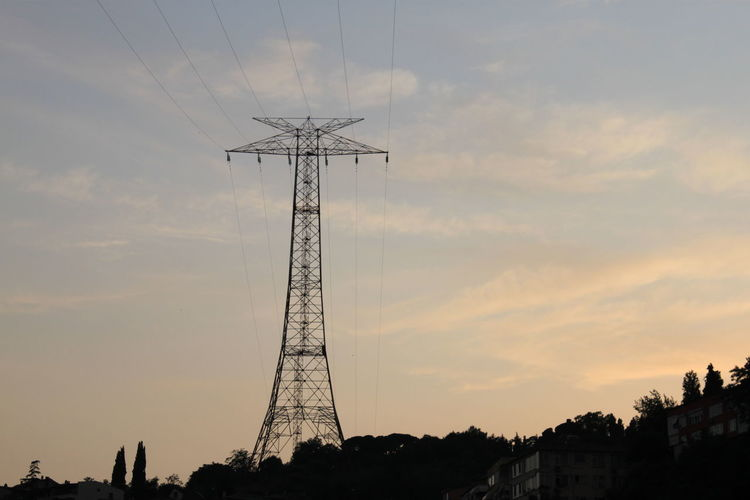 Silhouette electricity pylon and trees against sky at sunset