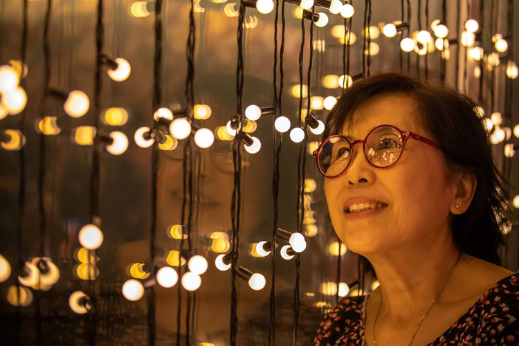 Portrait of smiling woman with illuminated lights at night