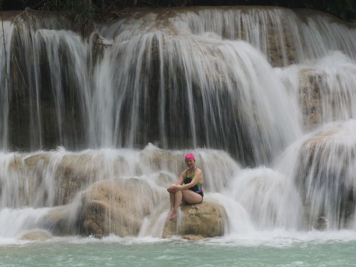 Woman sitting by waterfall on rock