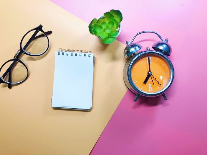 Directly above of eyeglasses with alarm clock and spiral notebook on colored background