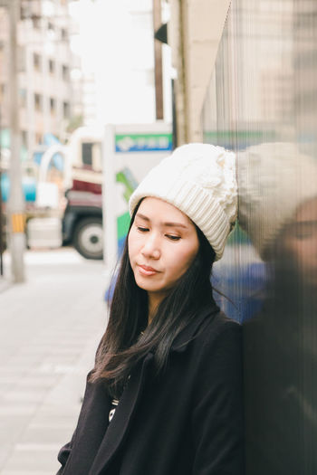 Thoughtful Woman In Knit Hat Standing By Wall