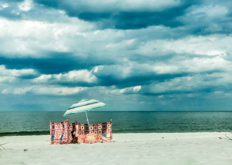 Beach Beauty In Nature Blue Cloud - Sky Day Horizon Over Water Nature No People Outdoors Postcard Sand Scenics Sea Sky Thunder Clouds Tranquil Scene Tranquility Travel Destinations Umbrella Vacations Water Windbreaker Woman EyeEmNewHere Vintage