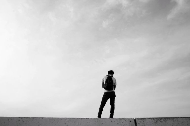 Rear view of man standing on wall against sky