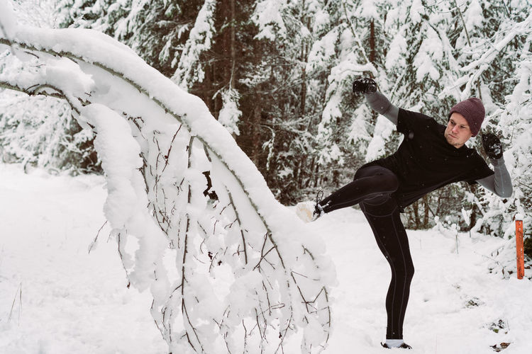 Young man kicking in the snow Activity Beauty In Nature Cold Temperature Day Forest Frozen Full Length Leisure Activity Lifestyles Nature One Person Outdoors People Real People Scenics Snow Sport Tree Warm Clothing Weather White Color Winter Young Adult Young Women Fresh On Market 2018