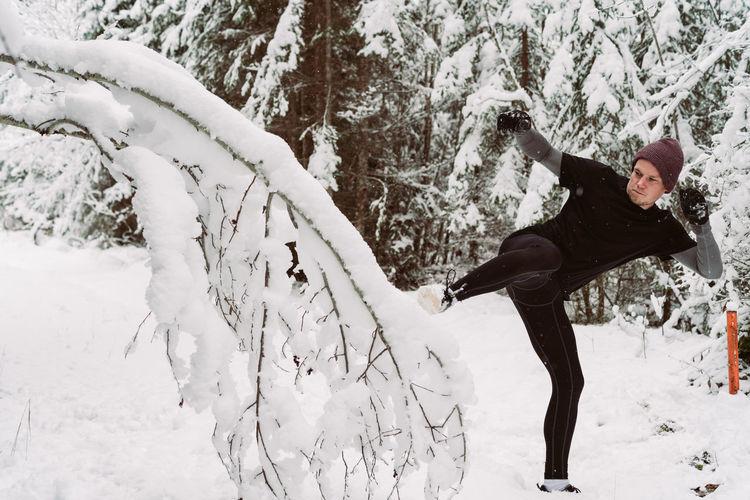 Man Kicking Snowy Tree