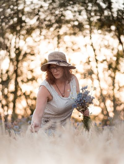 Mature Woman Holding Flower Between Cereal Plants Looking Away