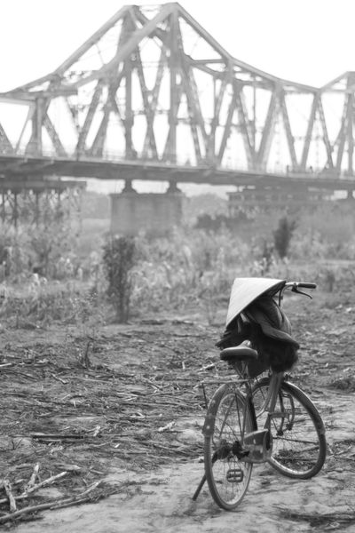 A bike parked in a rice paddy Abandoned Agriculture Bicycle Chinese Hat Connection Day Full Length Men Outdoors Rear View Rice Field Rice Paddy Road Street Tourism Traveling Vietnamese Hat Walking