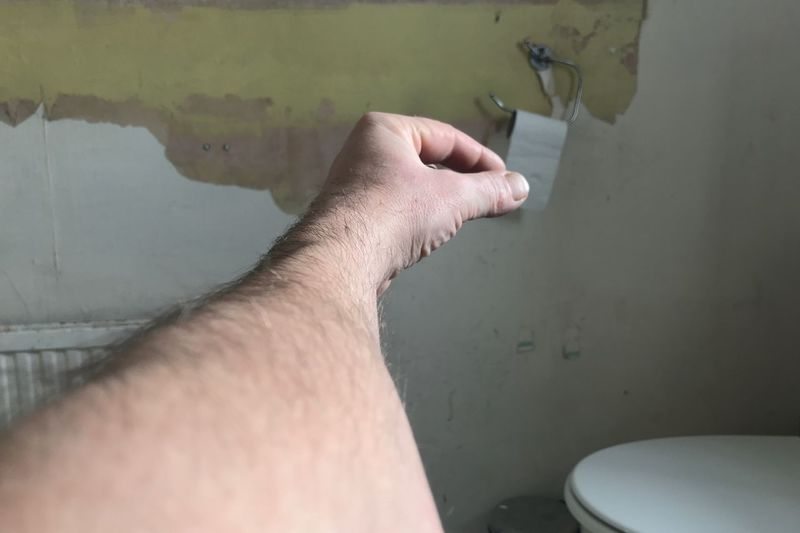 Optical illusion of man hand holding toilet paper in bathroom against wall