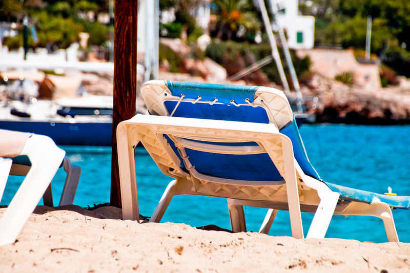 Empty chairs by swimming pool at beach