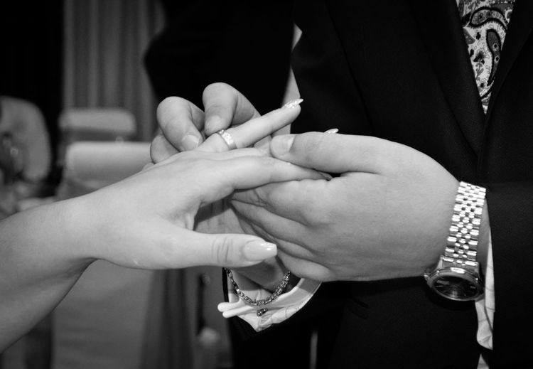 Midsection of groom wearing ring to bride in wedding ceremony
