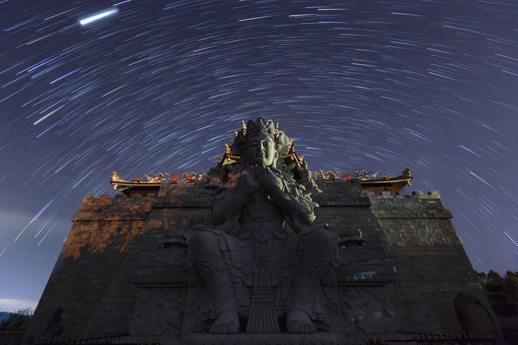 Low angle view of statue against star trail