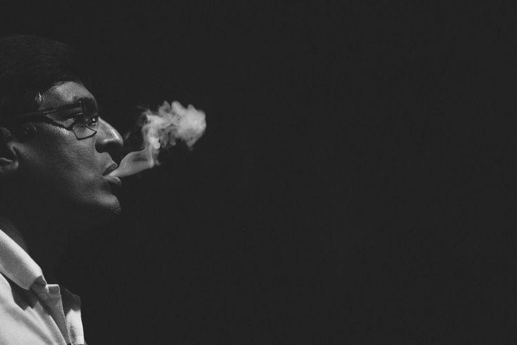 Side view of man blowing smoke